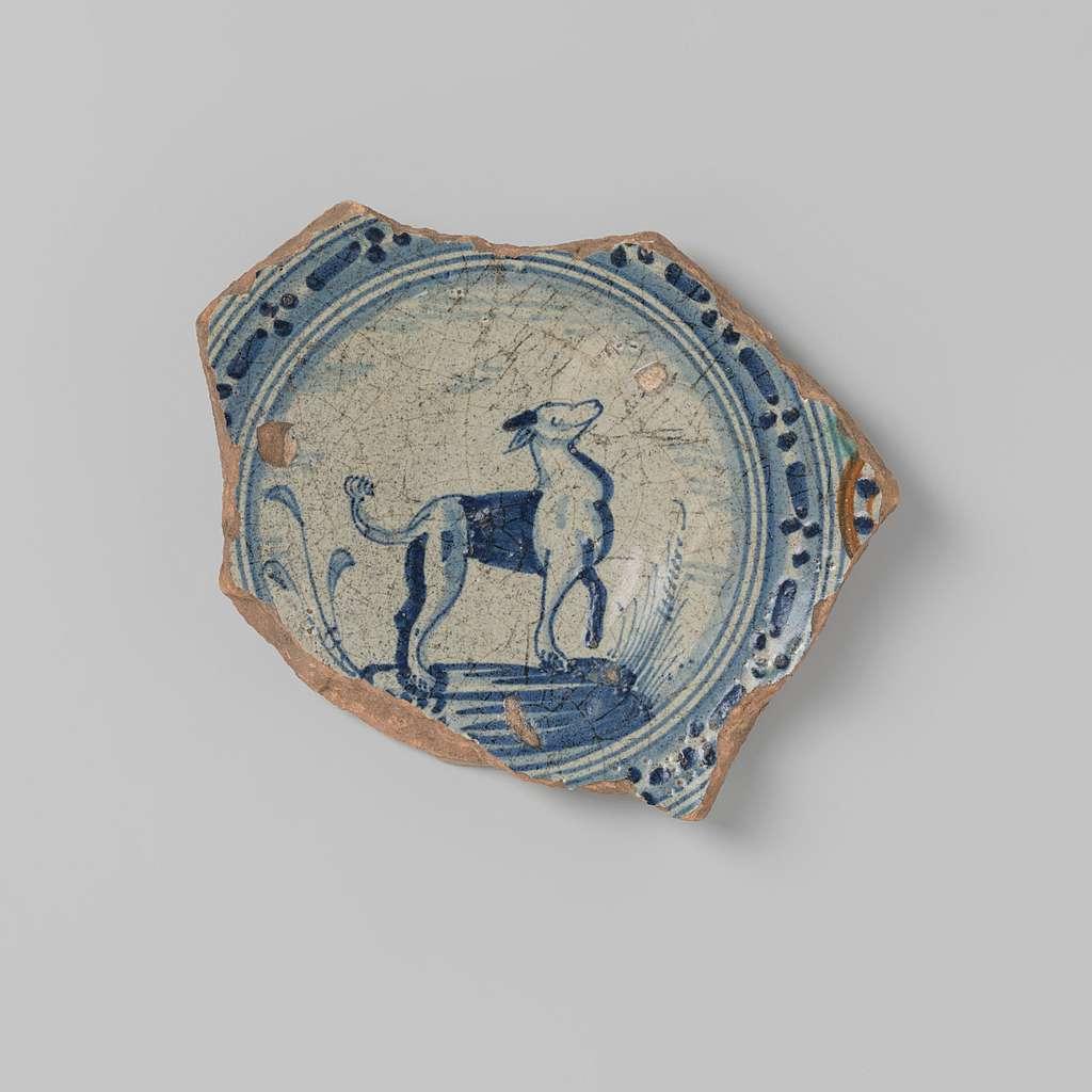 Schotelscherf van aardewerk voorzien van een tekening van een landschap met dier (hond of hert?) in blauw