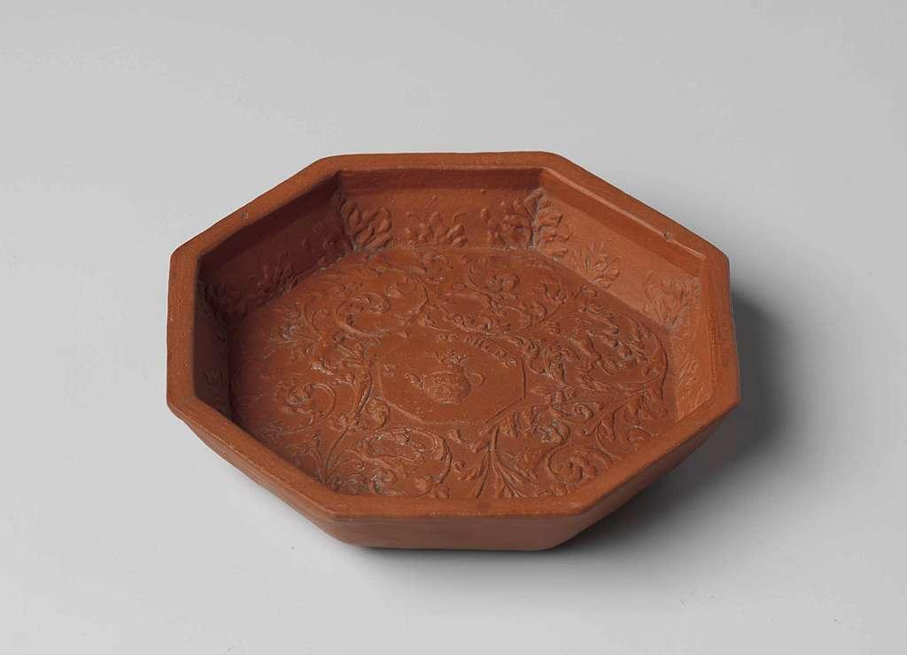 Schaal of teapotstand, achtkantig, van roodbakkend aardewerk. Bodem versierd met ranken in reliëf met gekroonde theepot.