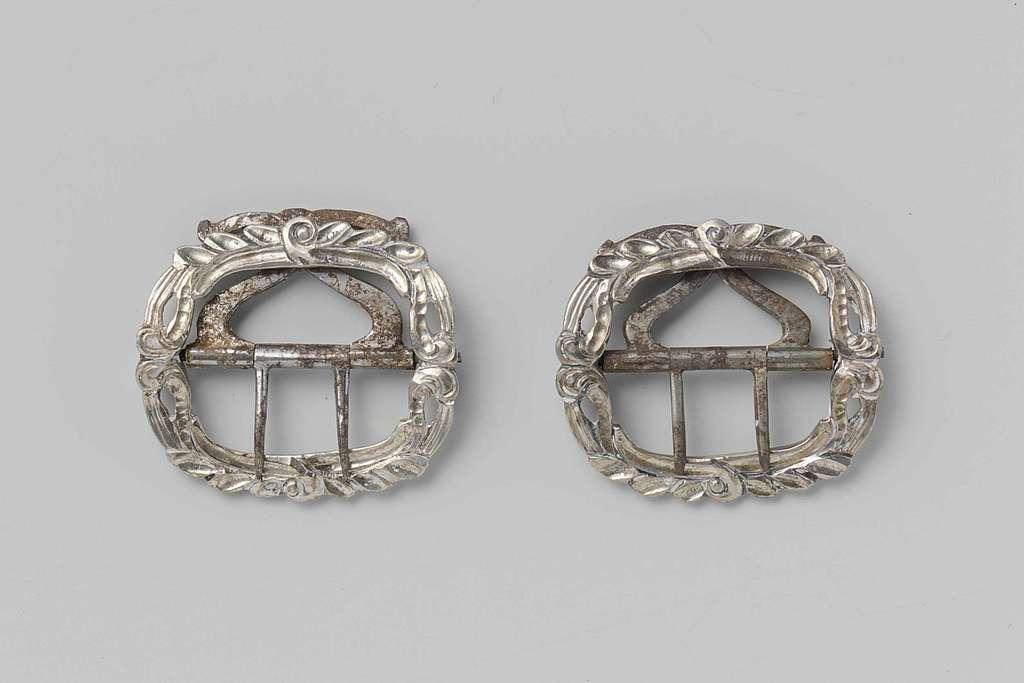 Gesp van zilver met gedecoreerde rand en een scharnierend deel waaraan twee tanden