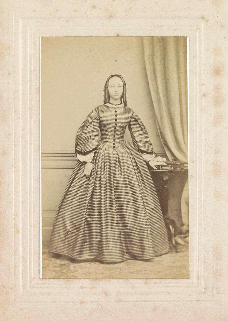 Portret van een jonge vrouw met een geruite jurk, staand