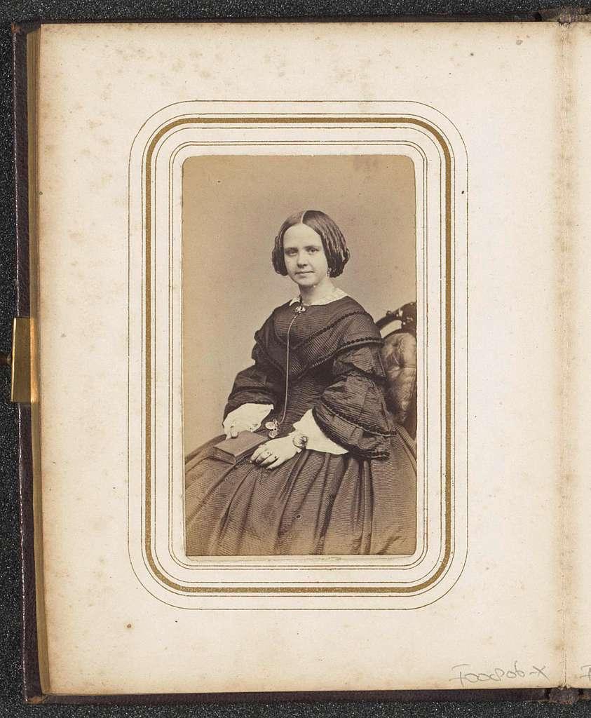 Portret van een zittende jonge vrouw met een boek op schoot