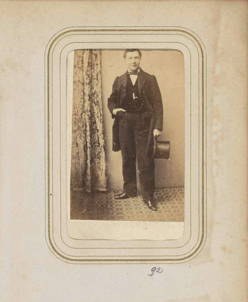 Portret van een man in een jas met een hoge hoed en hand in de zak