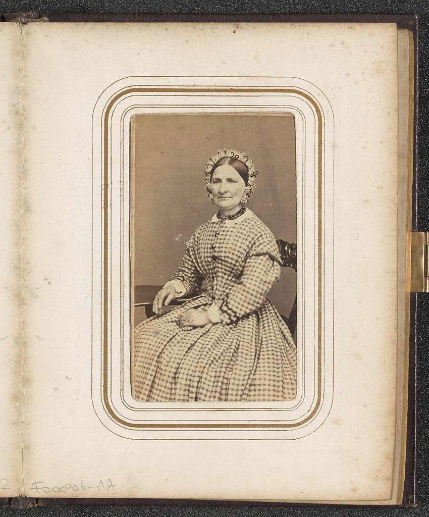 Portret van een zittende vrouw met een muts in een geruite jurk