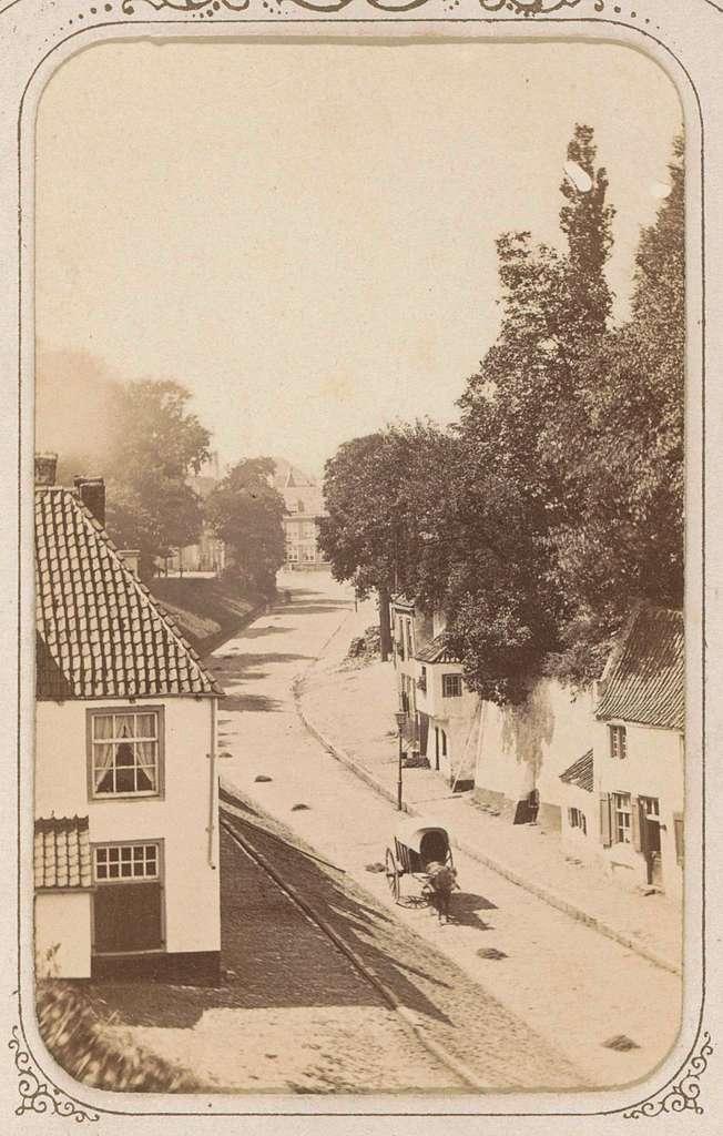Straatgezicht met een huifkar tussen huizen, vermoedelijk in Nederland