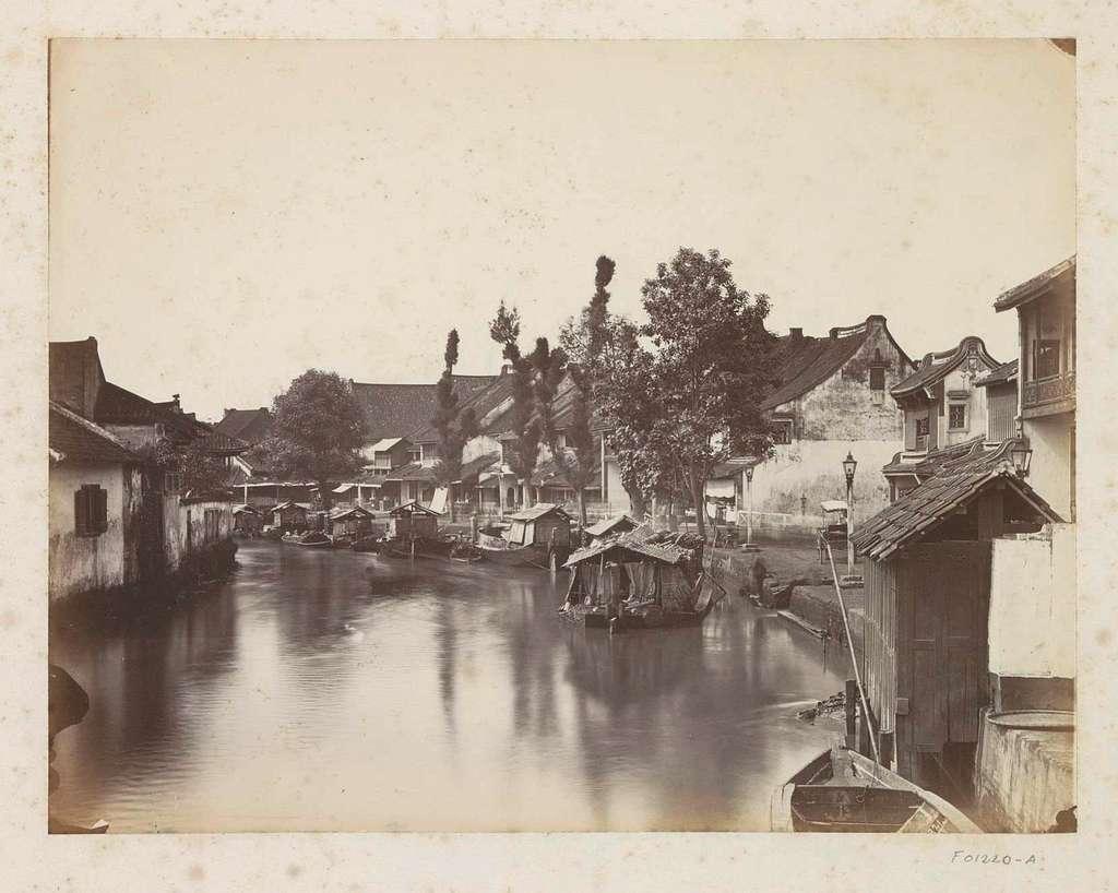 Gezicht op een rivierkade met huizen en boten op Java