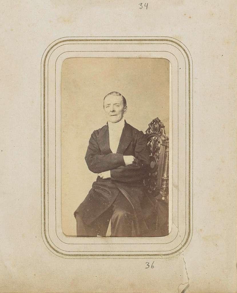 Portret van een zittende man met een lange jas