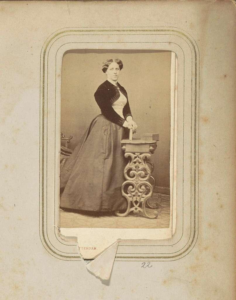 Portret van een vrouw met een lange rok en een bolero bij een tafeltje