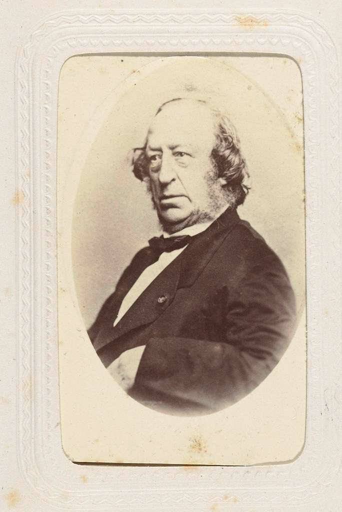Portret van een man met baard in colbert met strik