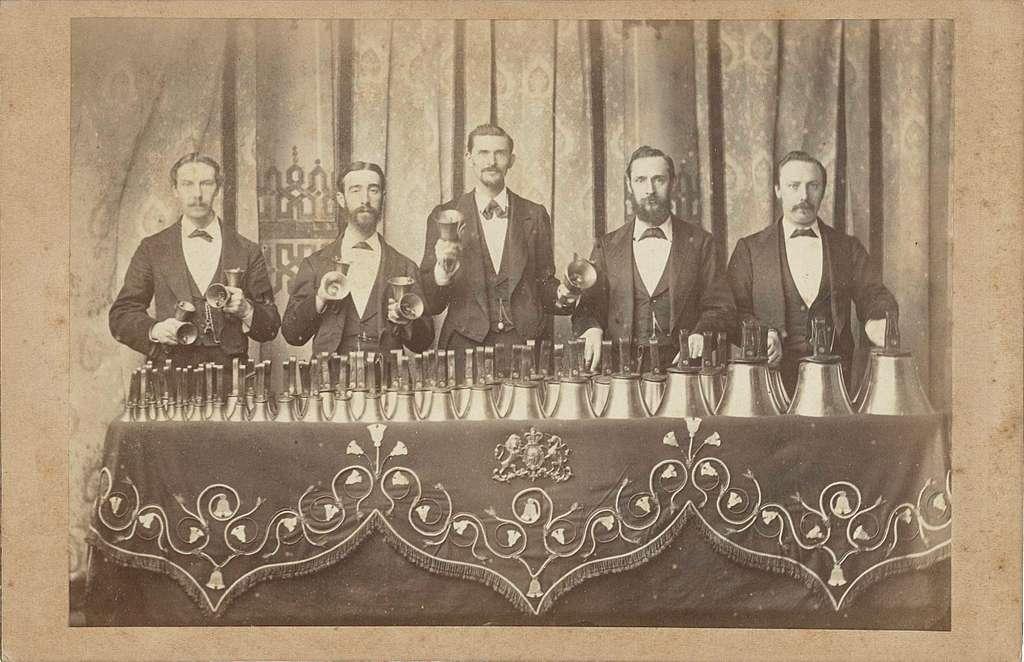 Groepsportret van 'De Koninklijke Klokkenspelers' uit Londen, met hun 131 klokken