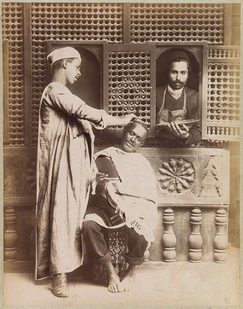 Portret van een kapper, een klant met spiegel en een bediende met schaal