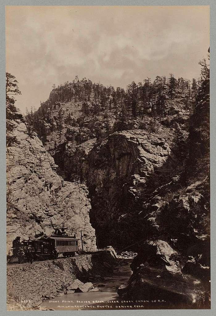 Mannen poserend naast een trein van de C.C.R.R. bij Stony Point in Clear Creek Canyon