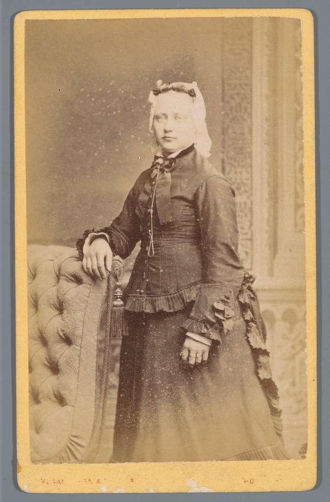Portret van een onbekende vrouw achter een fauteuil