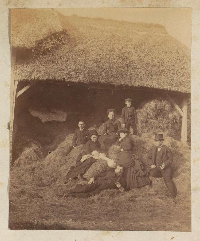 Groepsportret van een Franse familie bij een hooiberg