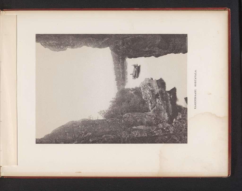 Gezicht op een stoomboot te water vanaf een plek tussen twee rotsen