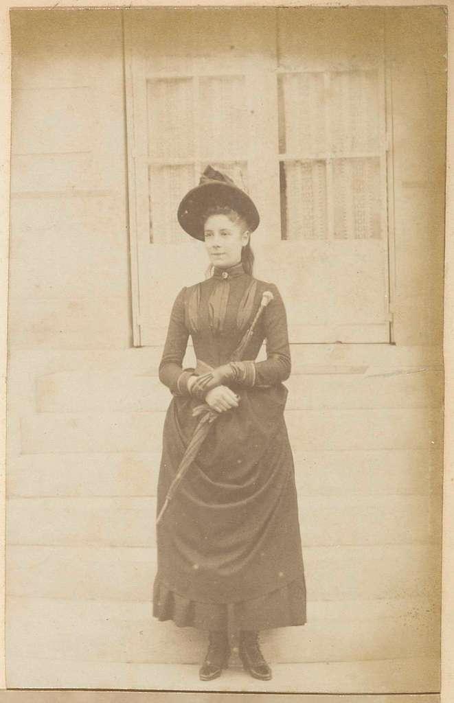 Portret van een Frans meisje met hoed en paraplu, staand op de trappen bij een huis