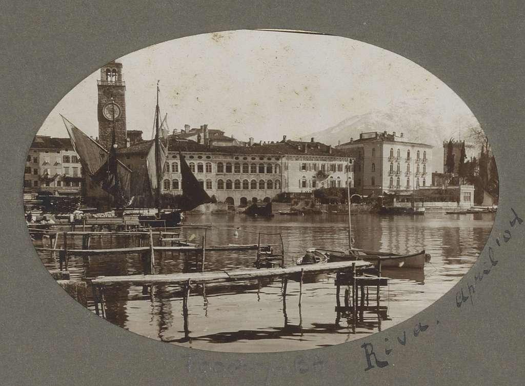 Gezicht op de haven van Riva del Garda met klokkentoren, gebouwen en omliggende bergen