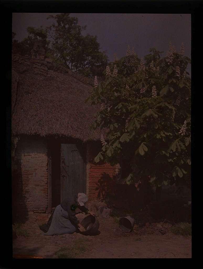 Vrouw met teil voor de deur van woning