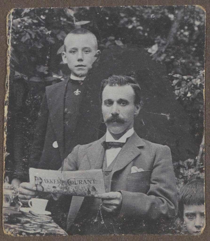 Portret van twee kinderen en een man met een krant (Bakker Courant) in de handen