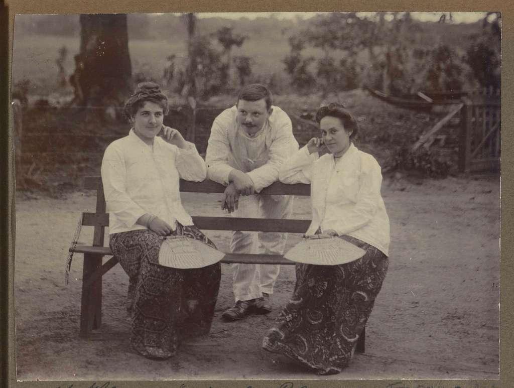 Twee zittende vrouwen en een man leunend op een bank, mogelijk in Suriname
